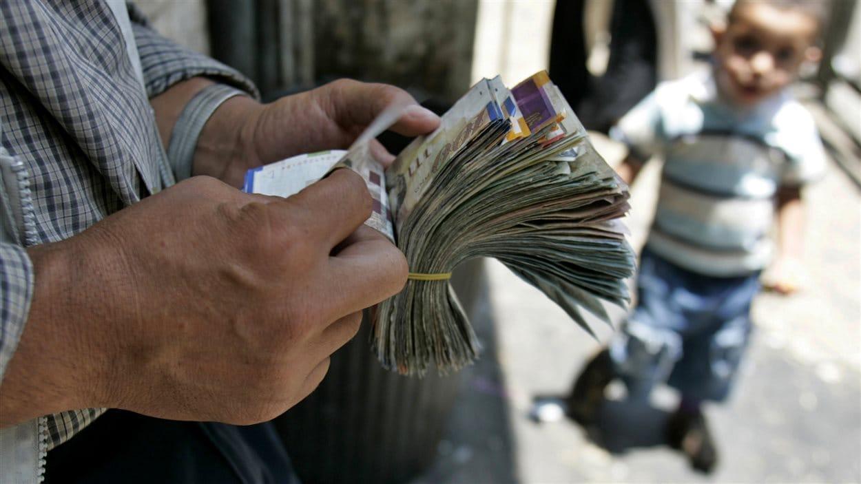 Un changeur palestinien compte ses billets dans une rue de Ramallah, en Cisjordanie.