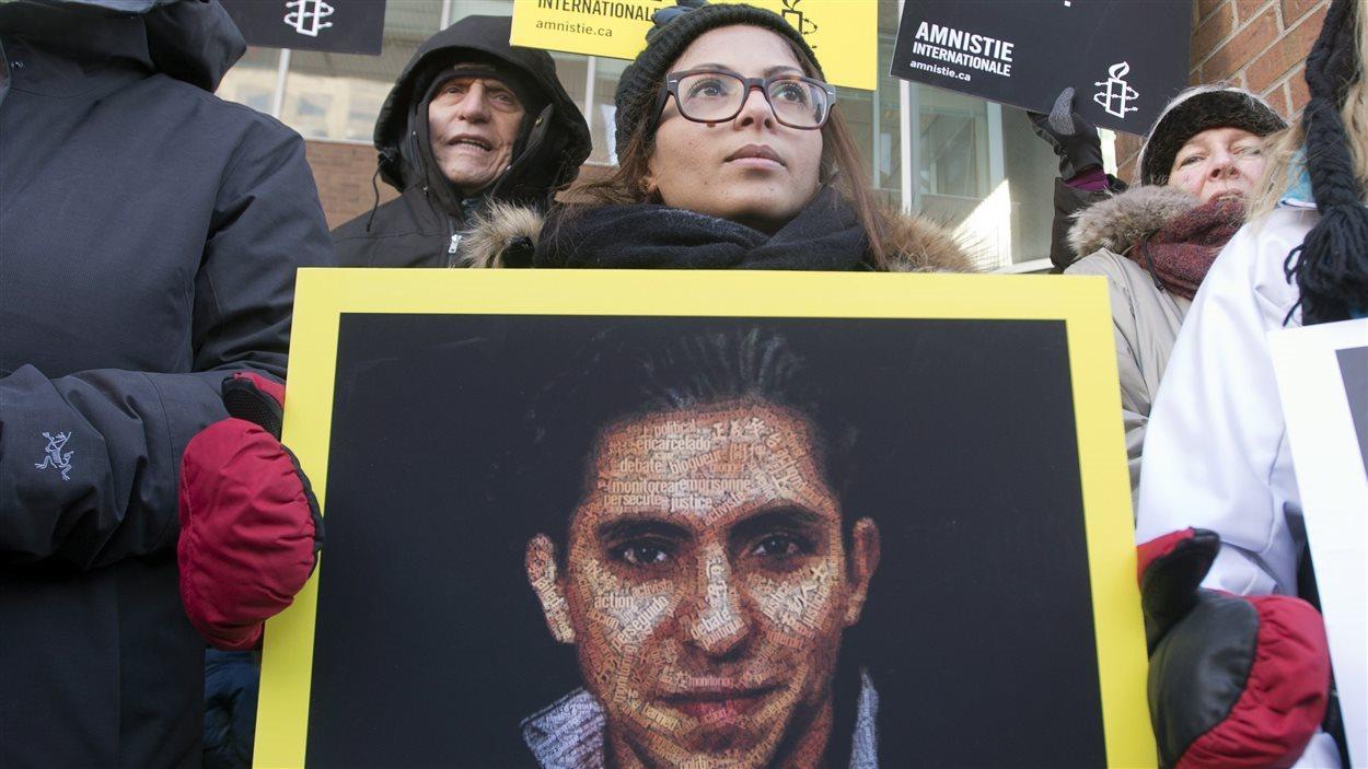 La femme de Raif Badawi, Ensaf Haidar, tient une photo de son mari lors d'une manifestation pour demander sa libération le 13 janvier 2015, à Montréal.