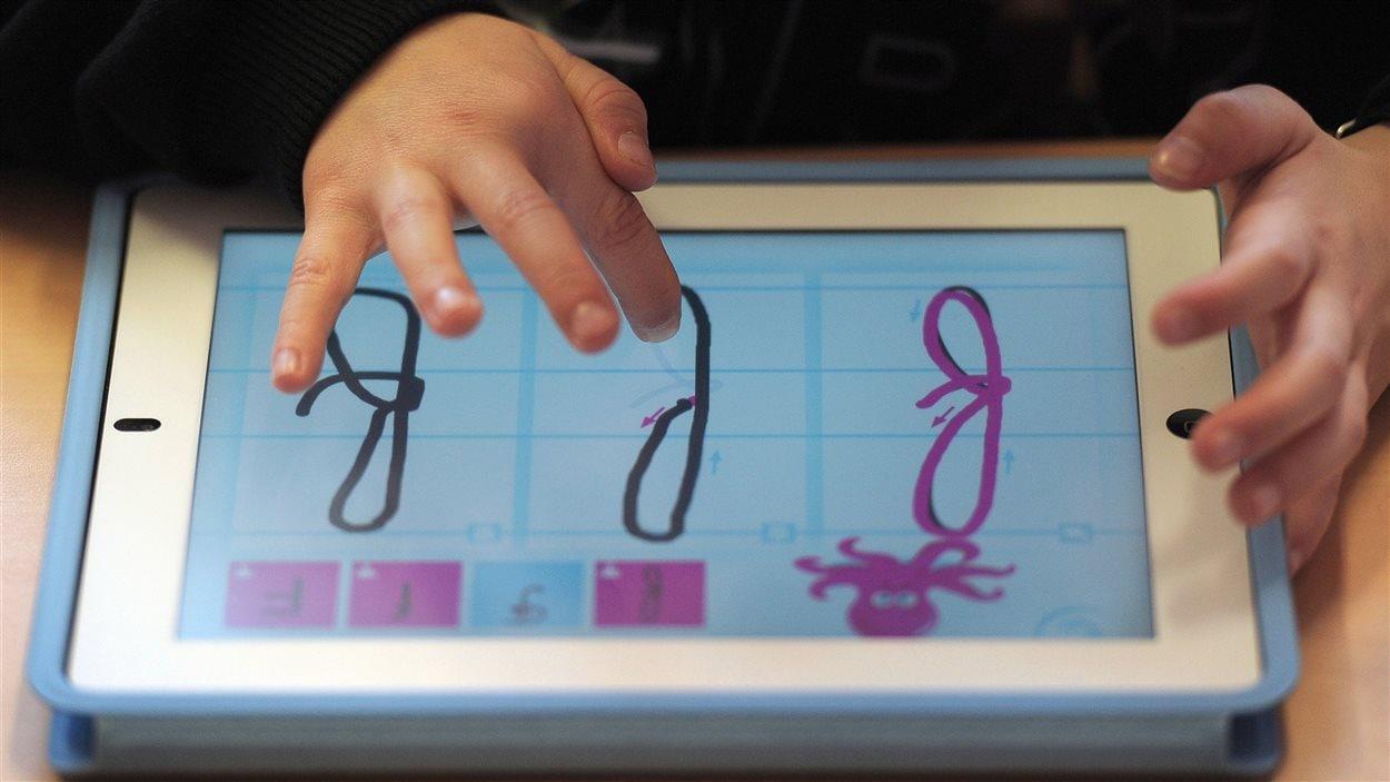 Un enfant apprend l'alphabet avec une tablette.
