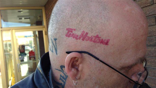 Korby Regan arbore un tatouage du logo de la chaîne de cafés Tim Hortons sur sa tête.