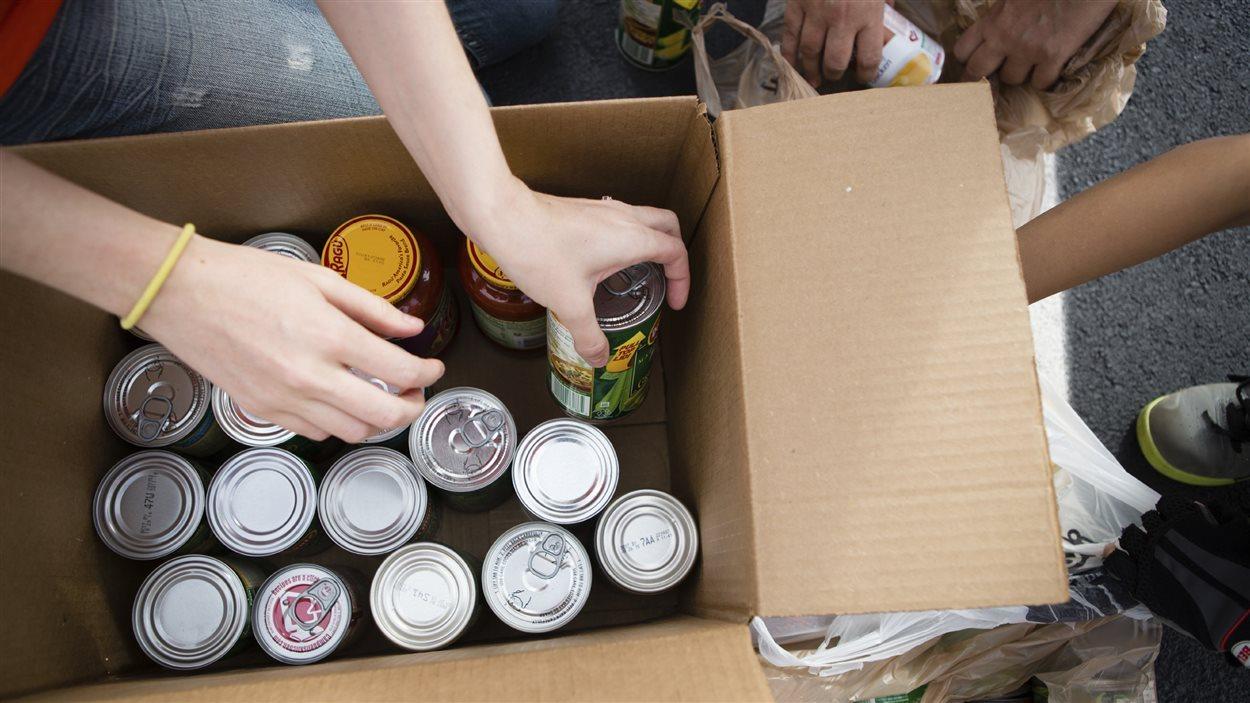 Un homme remplit une boîte de denrées non périssables.