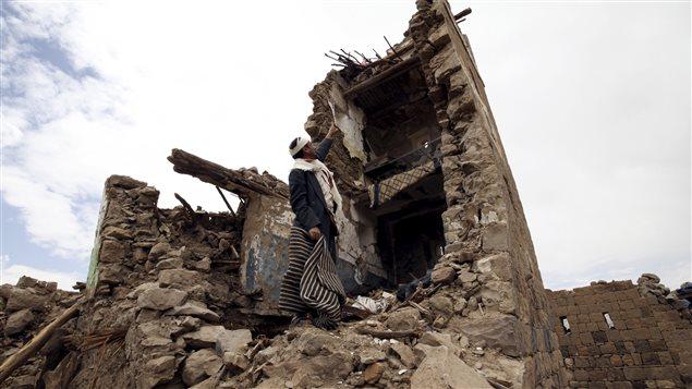 Un homme pointe ce qui reste d'une maison qui a été endommagée par les attaques aériennes de l'Arabie saoudite.
