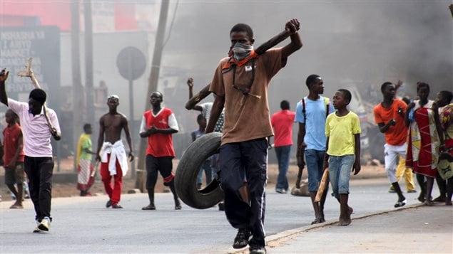 Un manifestant transporte un pneu pour ériger une barrière, lors d'une manifestation contre le dépôt de la nouvelle candidature du président sortant du Burundi.
