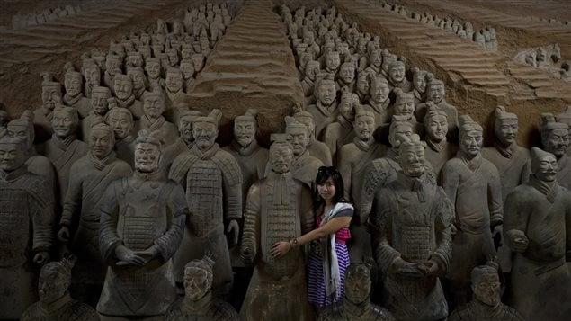 Une jeune femme enlace une copie des statues en terre cuite de l'armée de Qin Shi Huang au musée à Xi'an. (archives)