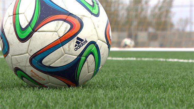 Un ballon de soccer sur un terrain synthétique