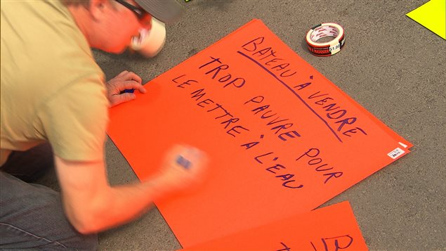 Un homme prépare une pancarte pour montrer son mécontentement face aux hausses des tarifs pour les rampes de mises à l'eau des municipalités.