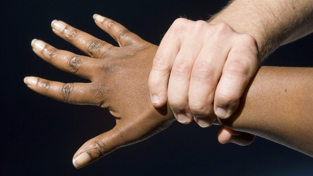 Un homme serre fortement la main d'une femme.