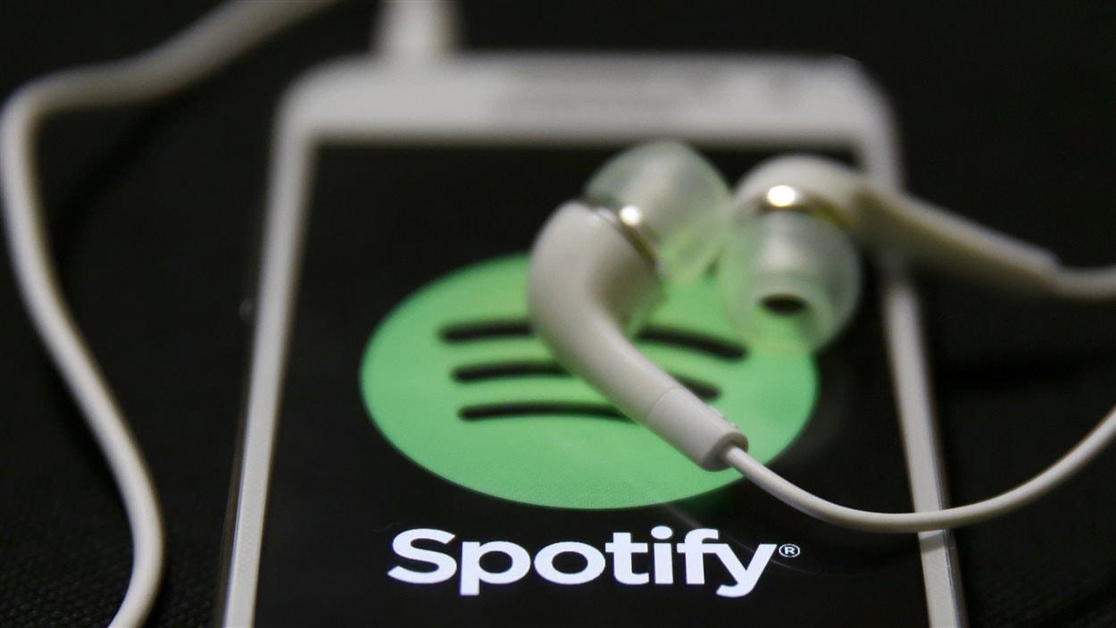 Des écouteurs et un téléphone intelligent branchés sur l'application Spotify