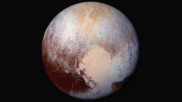 Une nouvelle photo de Pluton, dévoilée par la NASA le 24 juillet, dans laquelle les couleurs ont été saturées pour pouvoir détailler sa surface.