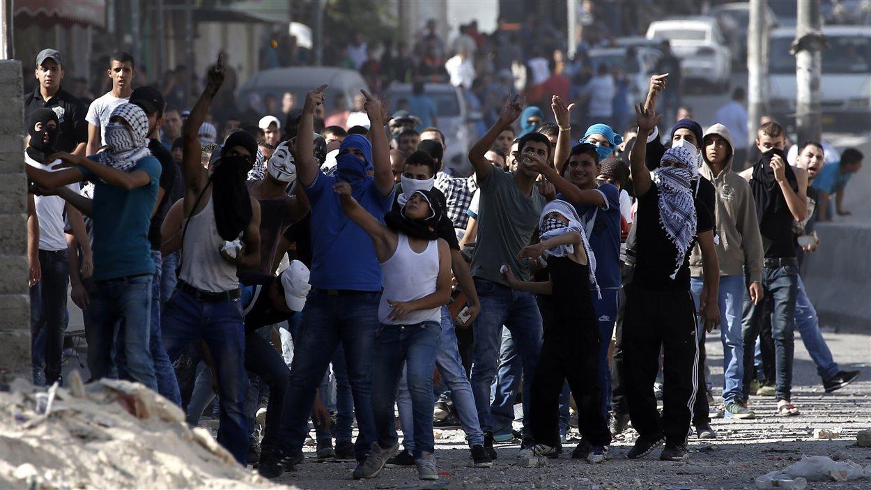 Des Palestiniens lancent des pierres à des soldats israéliens au point de passage de Qalandia, qui sépare Jérusalem de la Cisjordanie.