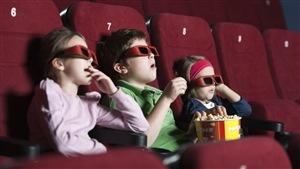 Des enfants au cinéma avec des lunettes 3D et mangeant du popcorn.