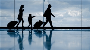 Une famille marche dans un aéroport.