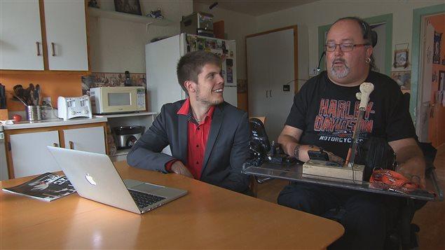 Samuel Fleurent-Beauchemin et Dany Martel regardent le bras JACO 3 doigts en action sur l'ordinateur portable