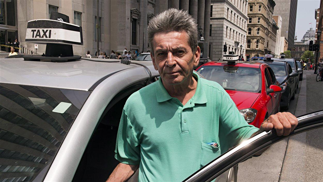 Ce chauffeur de taxi montréalais a presque 20 ans d'expérience. Il attend un client dans le Vieux-Montréal.
