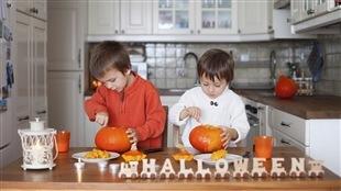 Deux enfants préparent des citrouilles pour l'Halloween.
