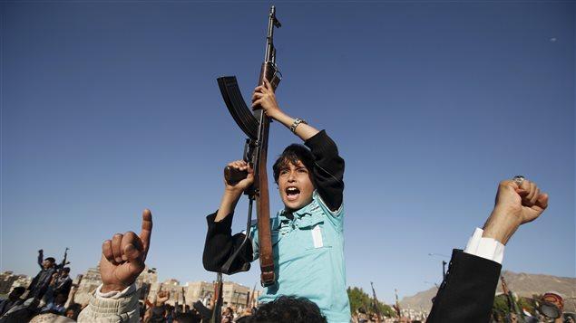 Un garçon tient une mitraillette lors d'une manifestation houleuse qui visait à dénoncer une grève menée par des travailleurs saoudiens à Sanaa