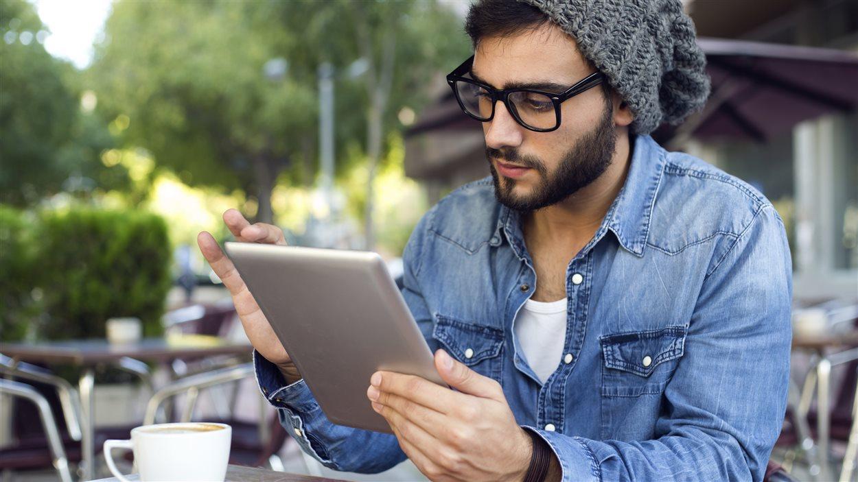 Un jeune homme avec sa tablette électronique dans un café