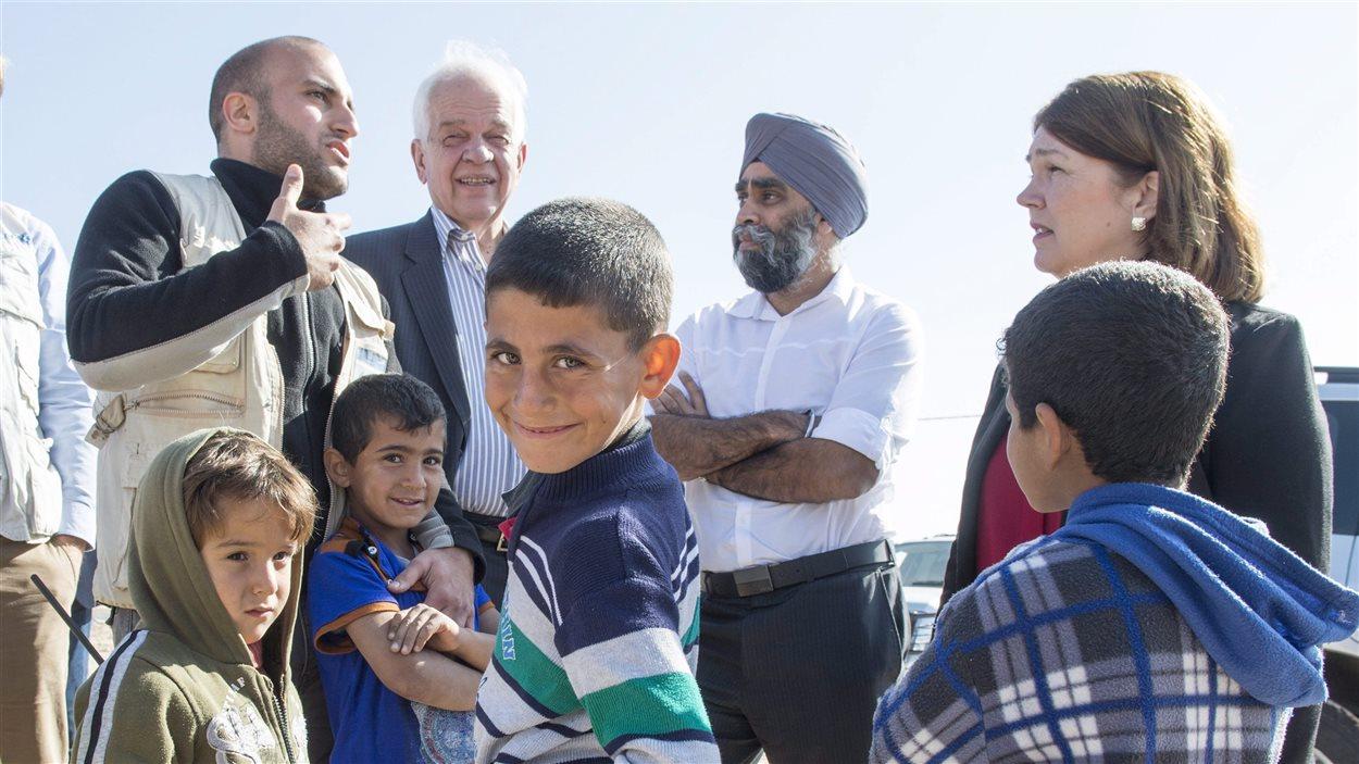 De jeunes Syriens entourent le ministre de l'Immigration, des Réfugiés et de la Citoyenneté John McCallum, le ministre de la Défense Harjit Sajjan et la ministre de la Santé Jane Philpott dans un camp de réfugiés en Jordanie le 29 novembre 2015.