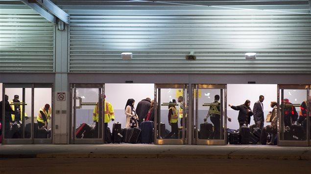 Les réfugiés syriens sont arrivés dans une aérogare aménagée pour eux à l'aéroport Pearson de Toronto.