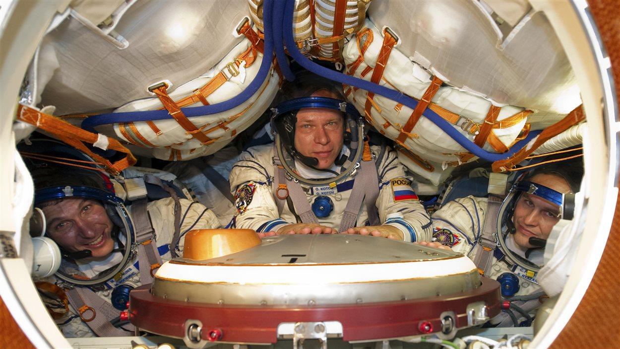 L'astronaute américain Michael Hopkins (G), et les cosmonautes russes Oleg Kotov (C) and Sergey Ryazanskiy dans une capsule Soyouz, à la base de Baïkonour, avant de partir pour la Station spatiale internationale.