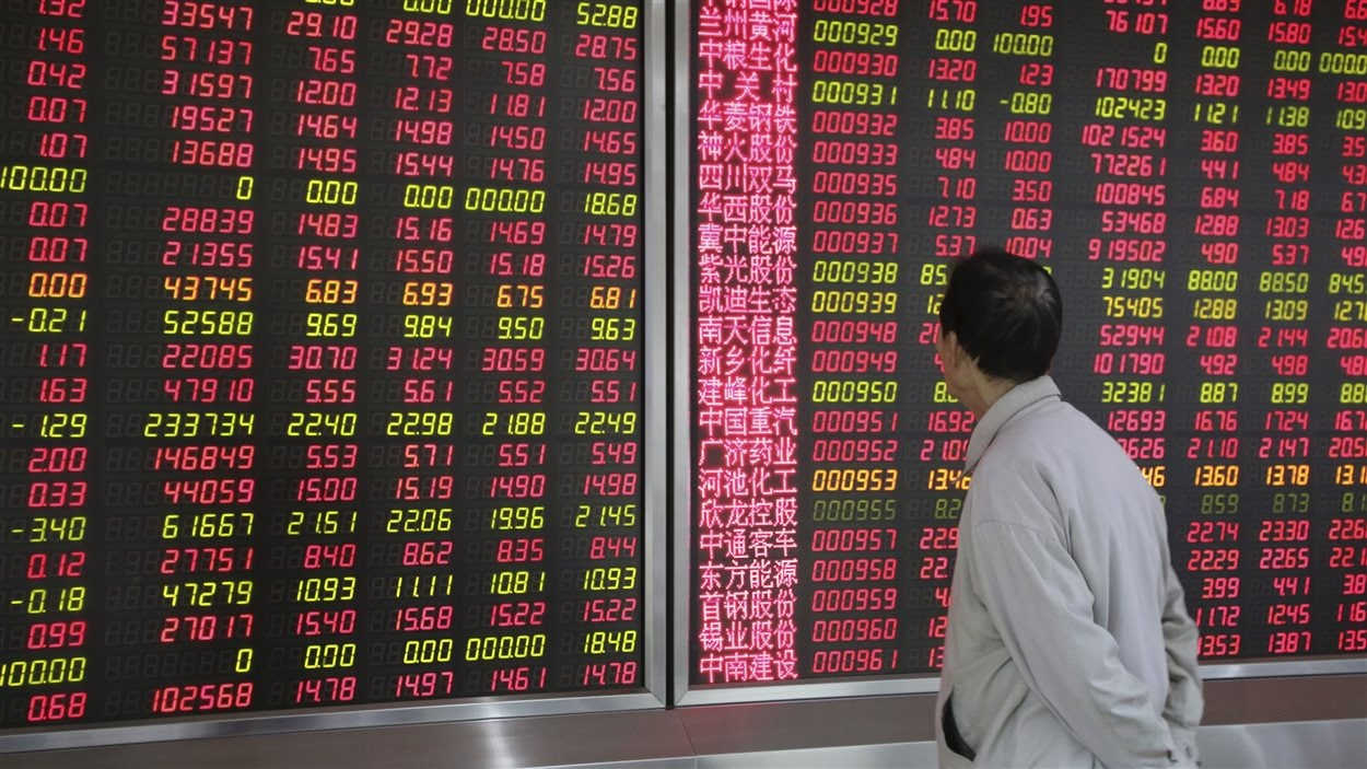 En début de journée, un investisseur regarde un tableau électronique affichant les informations sur les titres chez un courtier de Pékin.