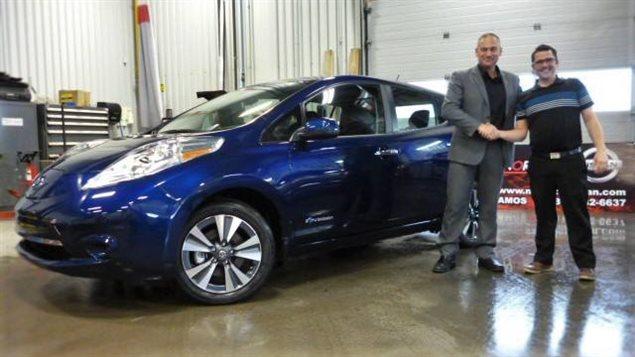 Le maire d'Amos, Sébastien D'Astous (à gauche), lors de l'achat de sa voiture électrique