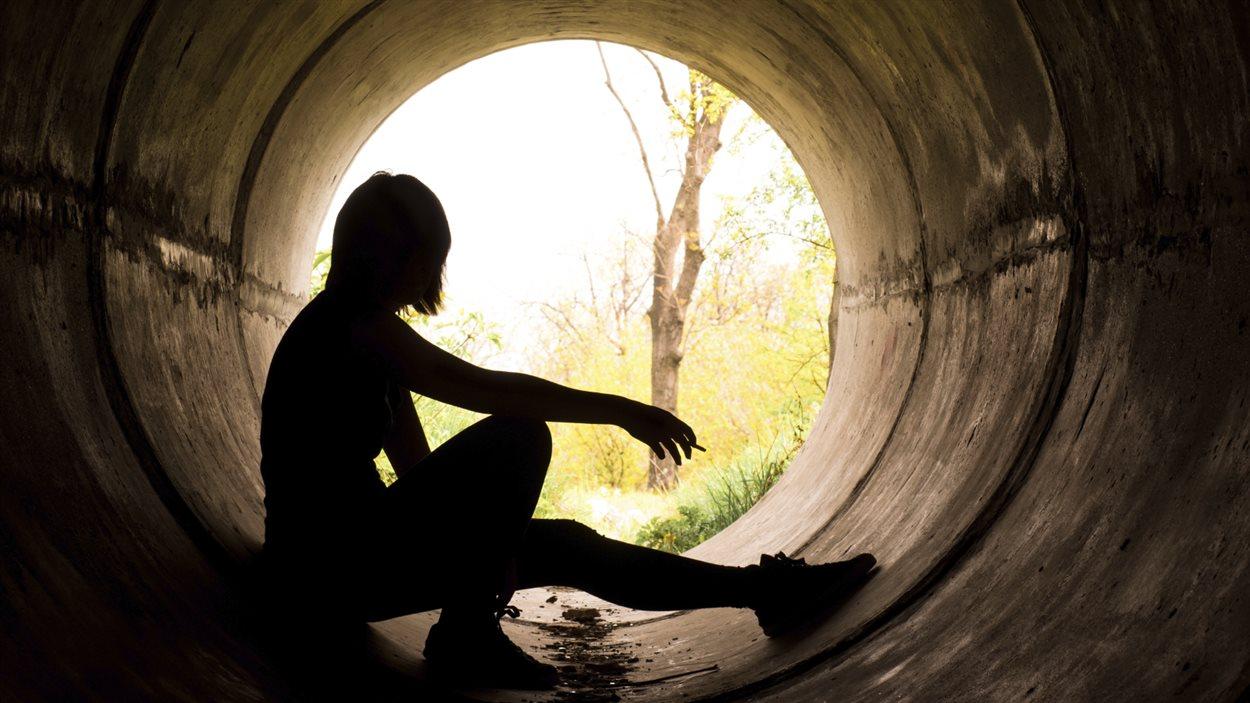 Une femme, dans un tunnel, fume une cigarette.