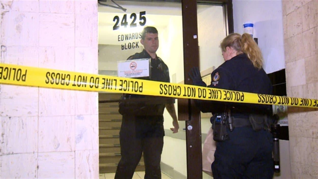 Des policiers à l'entrée de l'édifice où la mort suspecte a eu lieu.