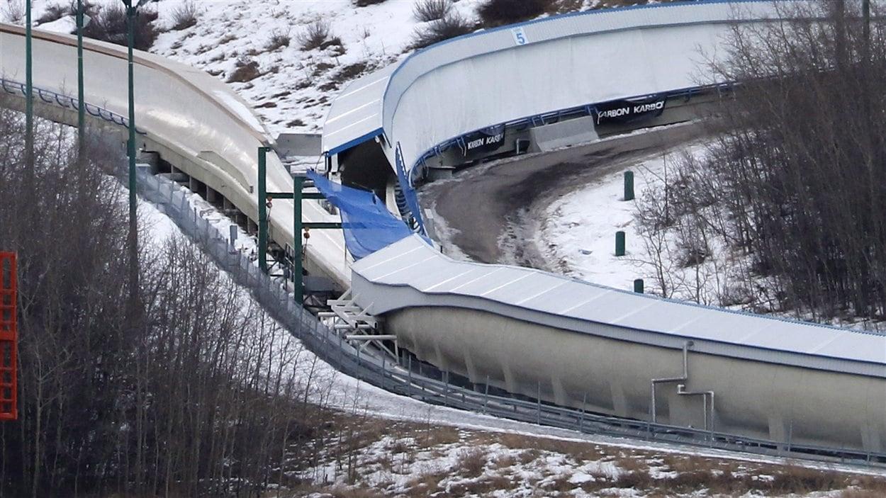 Une bâche couvre l'intersection entre les descentes de luge et de bobsleigh au Parc olympique de Calgary.