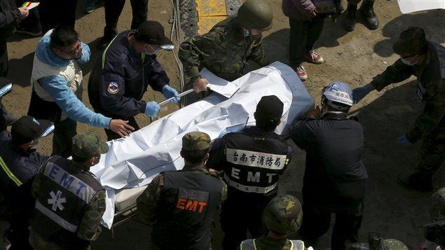 Des secouristes transportent le corps d'une victime du tremblement de terre à Tainan.
