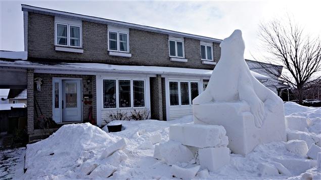 Le sculpteur travaille à partir d'un énorme bloc de neige.