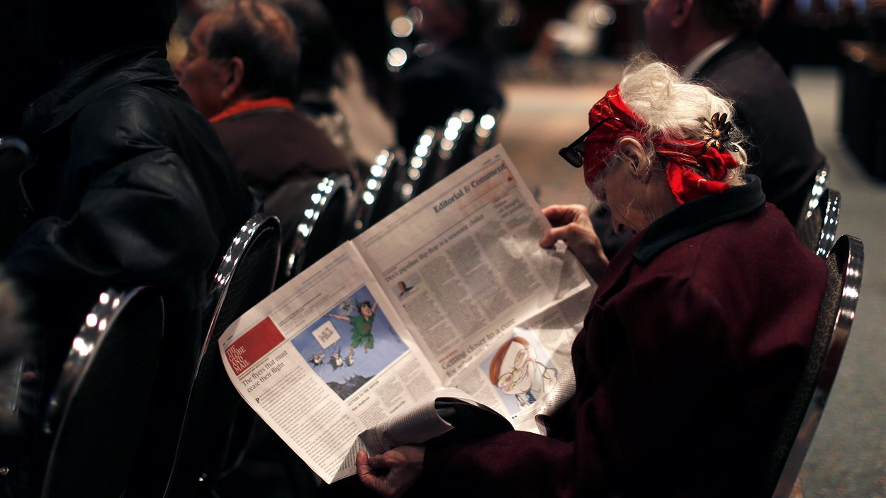 Une femme lit le journal Globe and Mail.