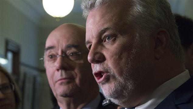 Flanqué de son ministre des Transports, Jacques Daoust, le premier ministre Philippe Couillard défend l'investissement du gouvernement dans la C Series de Bombardier.