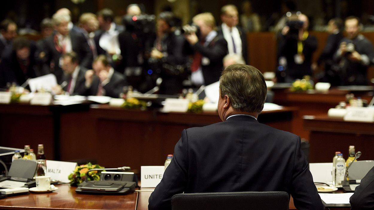 Le premier ministre britannique David Cameron prend place à la table des négociations.