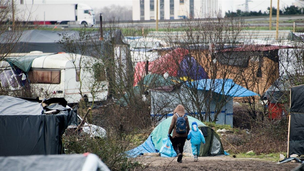 Une migrante marche avec son fils dans la « Jungle » de Calais.