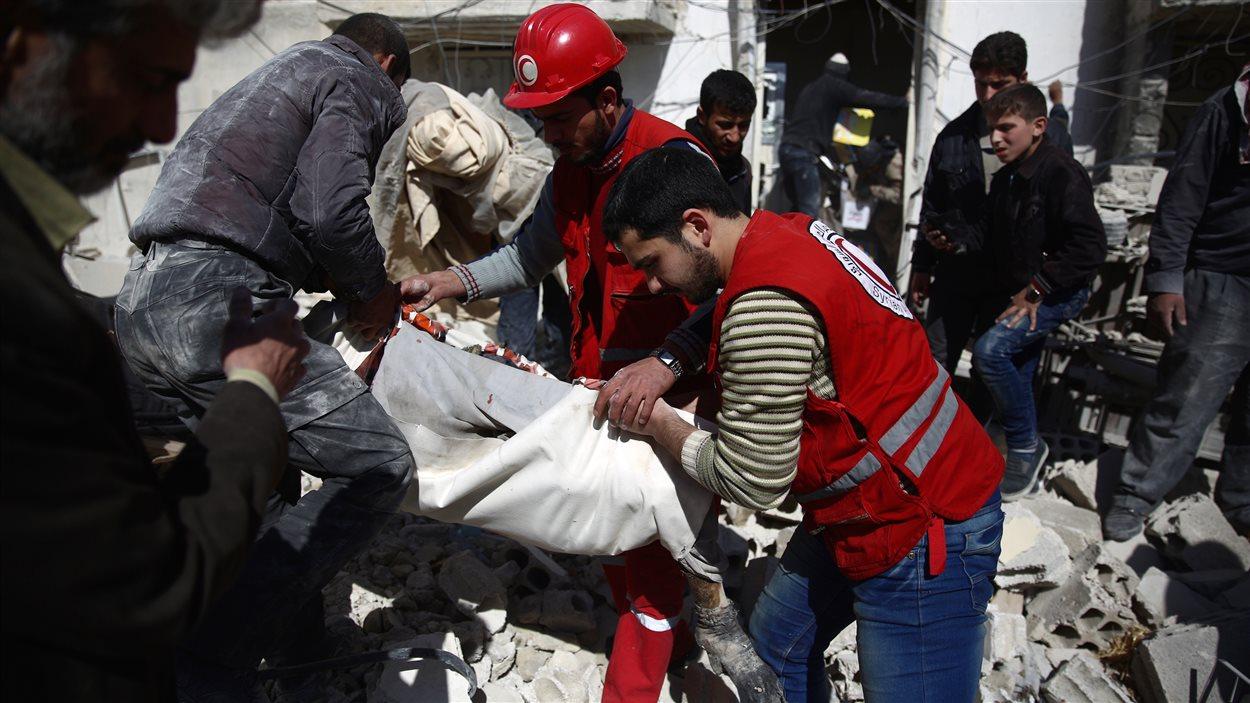 Des membres du Croissant rouge arabe syrien extirpent un corps des décombres, vendredi, à Douma.