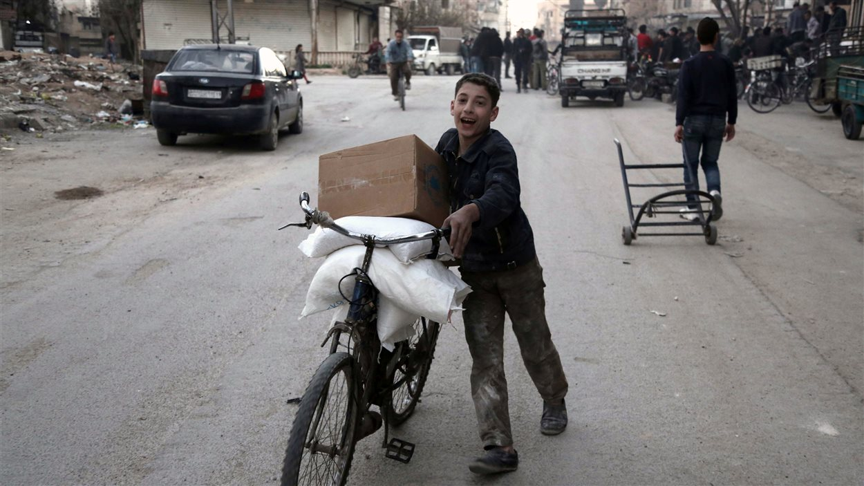Un garçon transporte des sacs transportant notamment du riz à Kafr Batna, mardi.