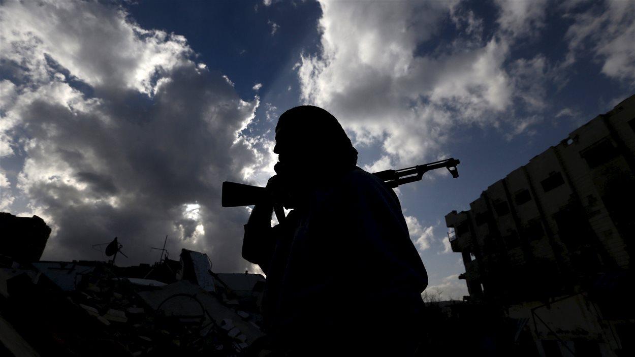 Un rebelle syrien transporte son arme sur son épaule.