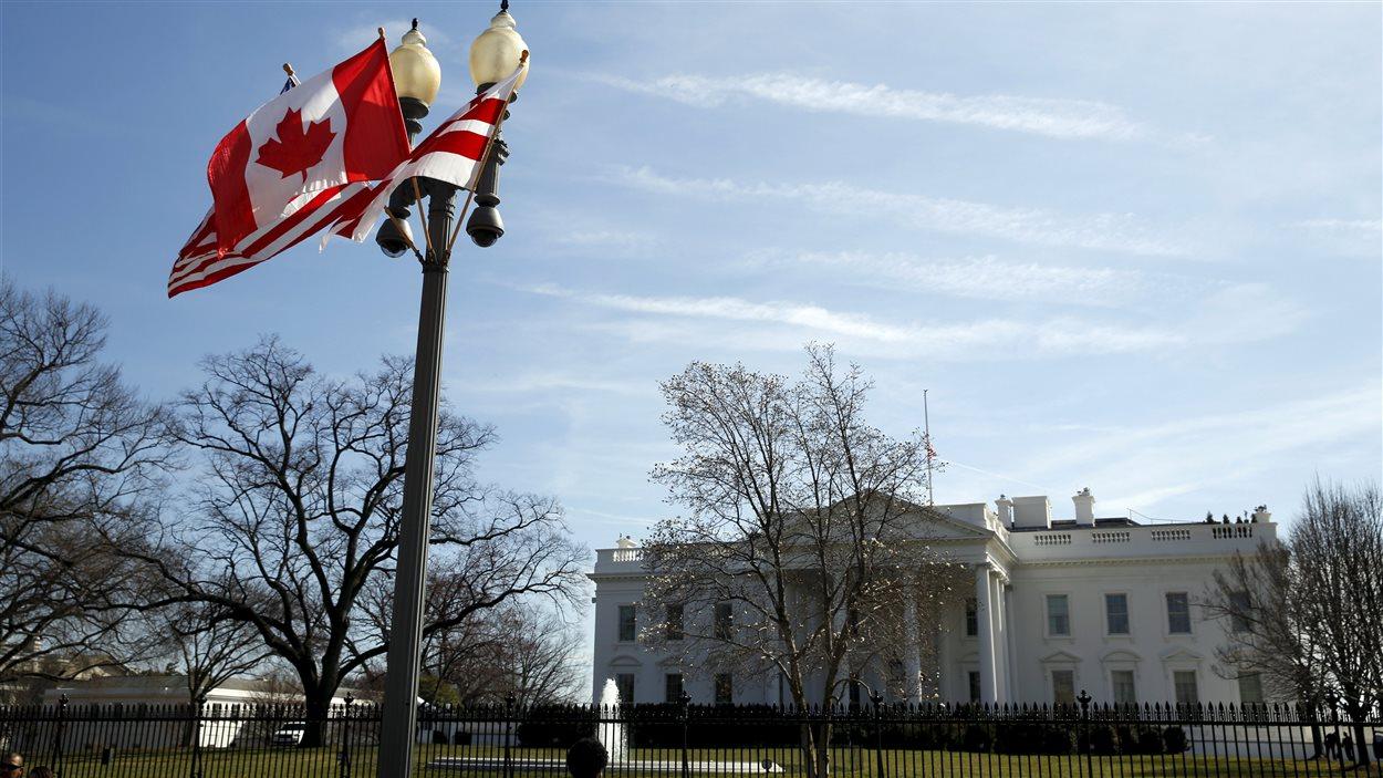 Les drapeaux canadien et américain flottent devant la Maison-Blanche, le 7 mars 2016.
