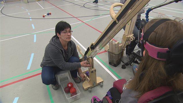 Josée Duquette se tient dos au jeu et manipule une rampe de lancement pour permettre à sa fille de lancer les boules.