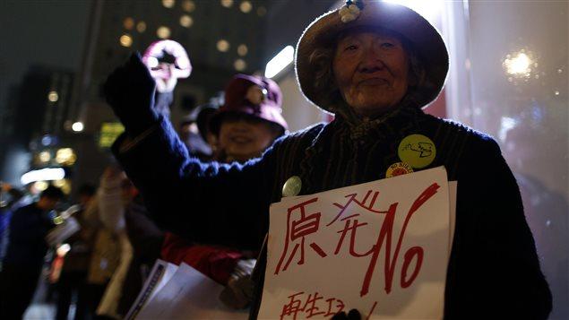 Une militante antinucléaire manifeste devant le siège social de la compagnie Tepco.