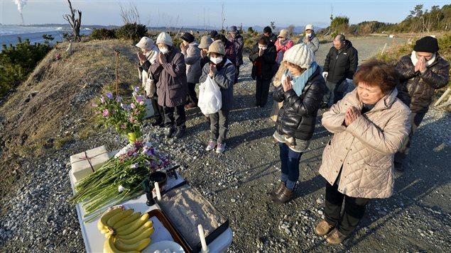 Des gens prient en mémoire des victimes de Fukushima, le 11 mars 2016, à Minamisoma.