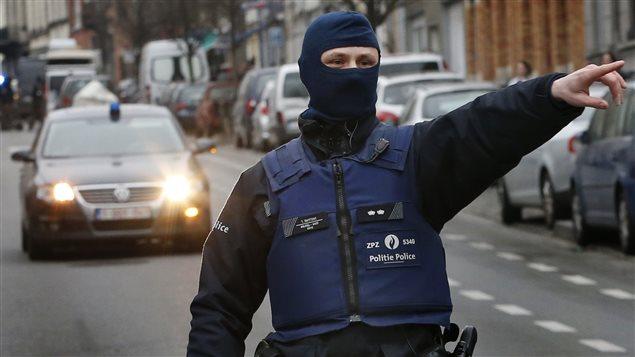 Un policier dans la connune de Molenbeek, près de Bruxelles, pendant une vaste opération pour retrouver Salah Abdeslam
