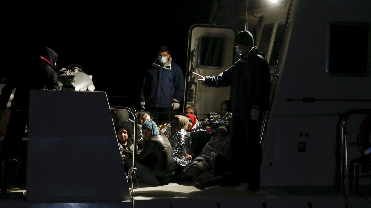 Des garde-côtes grecs encadrent des migrants arrivés sur l'île de Lesbos dans la nuit de dimanche à lundi.