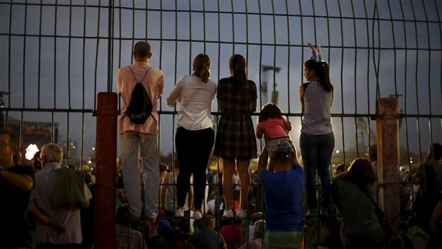 De jeunes spectateurs s'accrochent même à la barrière pour mieux voir la scène.