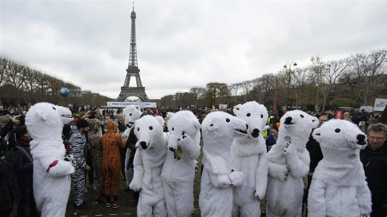 Des environnementalistes se sont rassemblés à Paris alors que les organisateurs du sommet sur le climat présentaient leur projet d'accord final en décembre 2015.