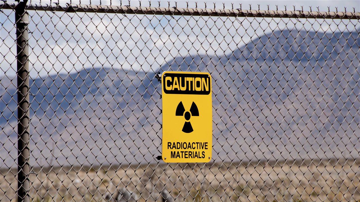 Un avertissement de matériaux radioactifs apposé à une clôture