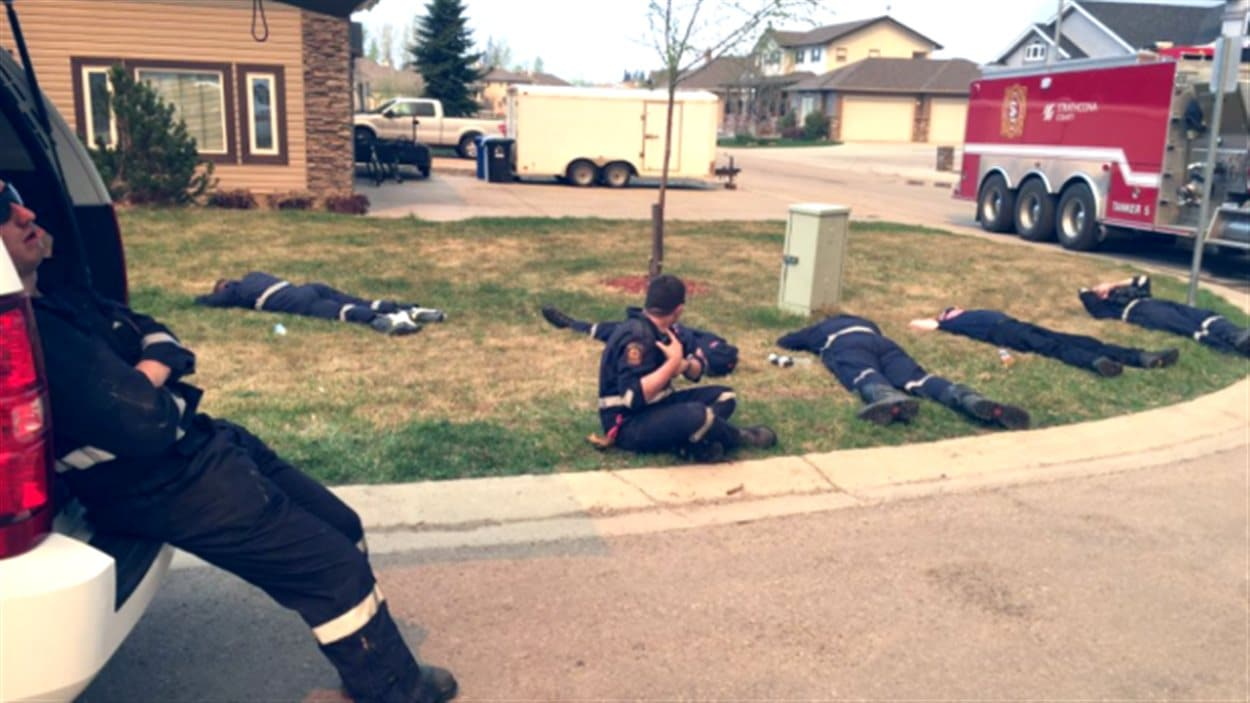 Des pompiers du comté de Strathcona se reposent pour la première fois en 30 heures à Fort McMurray, dans une photo publiée sur Twitter le 4 mai 2016 par le service incendie du comté.