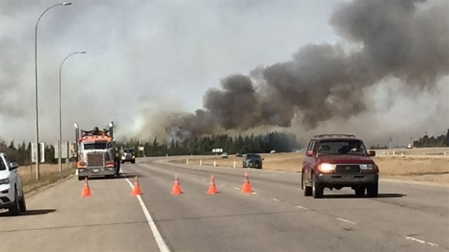 Le feu brûle tandis que les évacués quittent Fort McMurray