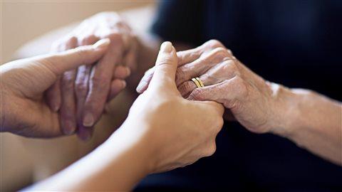 Une personne âgée et une personne plus jeune se tiennent pas la main.